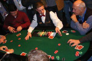 Ao centro, um Crupiê comanda a mesa em um jogo de cartas