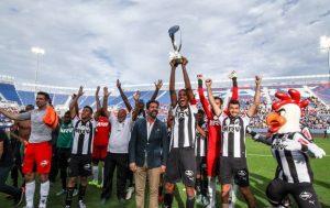 Jogadores e departamento técnico comemorando a conquista do torneio.