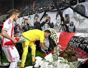 Jogadores do Olympiacos colocam flores no memorial, faixa com os rostos dos mortos ao fundo.