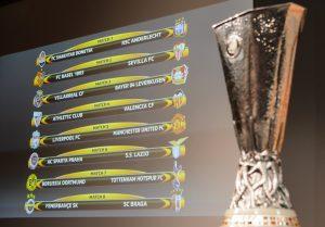 Taça da Liga Europa e a tabela das oitavas de final ao fundo durante o evento na Suíça.